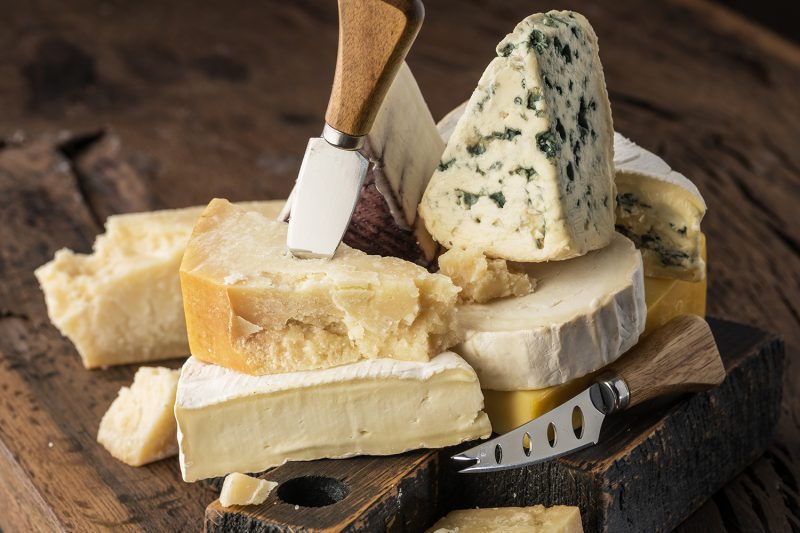 Assortment of different cheese types on wooden background. Cheese background.