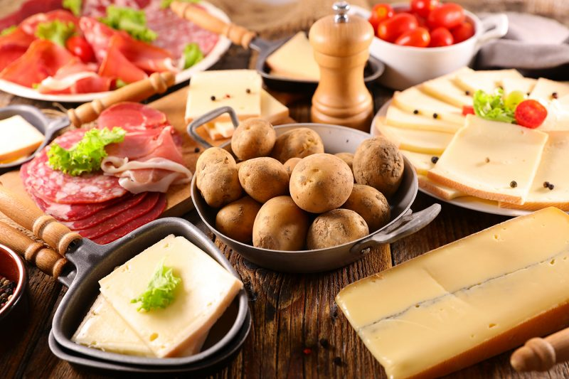 traditional raclette cheese party on wood background