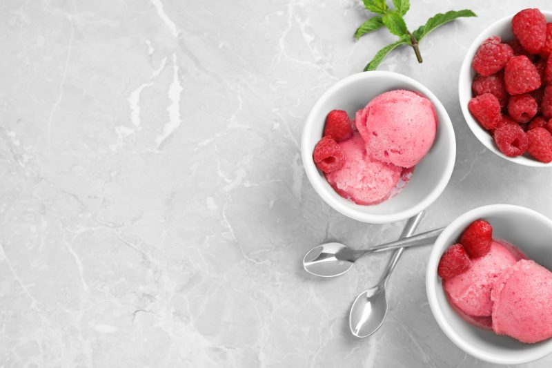 Flat lay composition with delicious raspberry ice cream on grey marble table, space for text