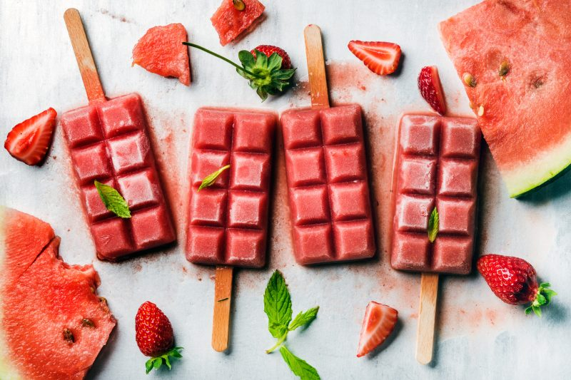 Strawberry watermelon ice cream popsicles with mint over steel tray background. Top view