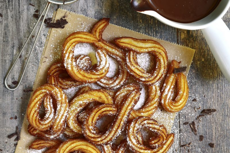 Traditional mexican dessert churros with chocolate sause on a rustic background.