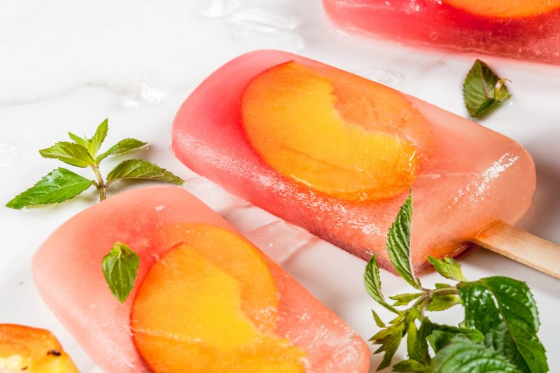 Summer desserts. Frozen drinks. Sweet fruit popsicles from frozen peach tea with mint. On a white marble table, with ingredients - peaches, mint, ice. Copy space