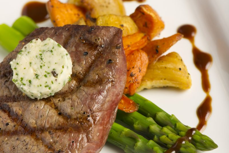 Gegrilltes Steak auf feinem Gemüse mit Kräuterbutter
