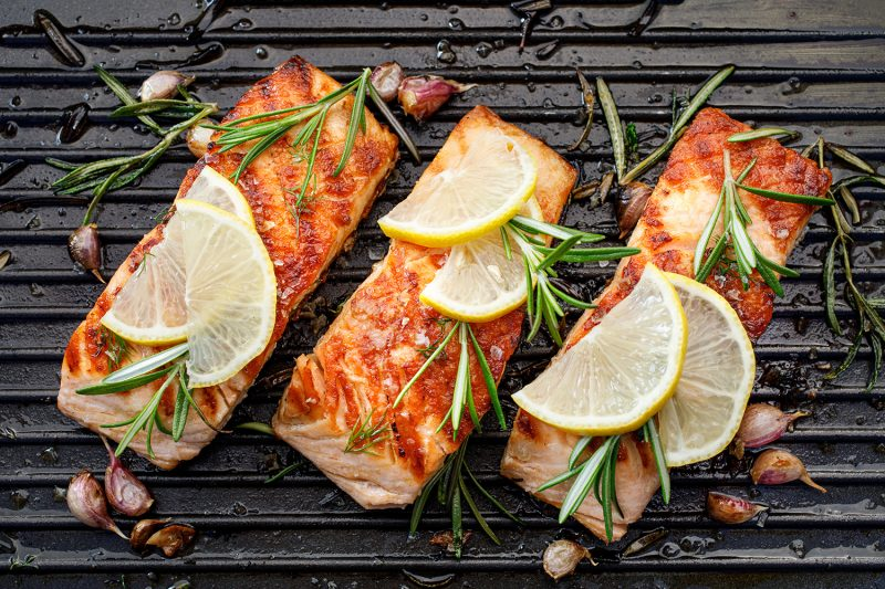 Grilled salmon fillets with fresh herbs and lemon slices on a grill,  top view
